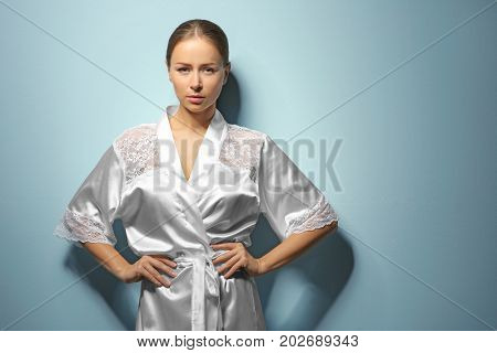 Beautiful young woman after shower in silk bathrobe on light background