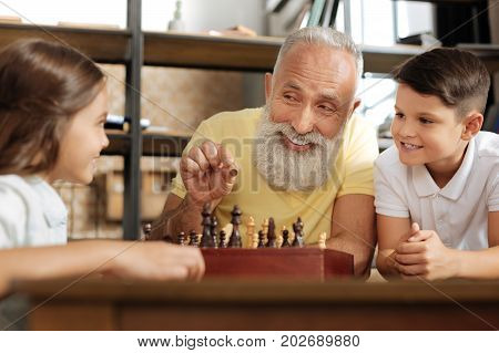 Best explanation. Pleasant senior man holding a pawn and showing to his grandchildren how to make a move with it, while smiling happily at them