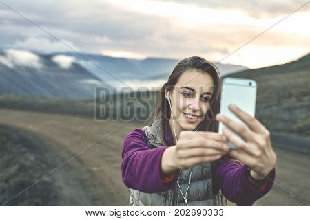 Girl in warm clothing makes selfie photo on background of mountains and sea of Iceland. women on the road thru a mountain pass, fjord is on background