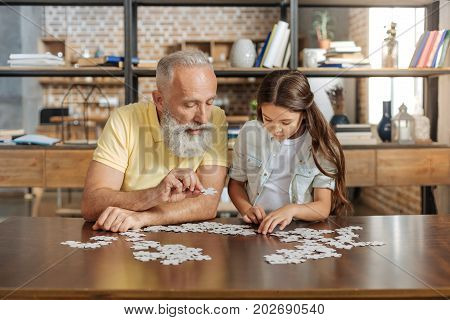 Maximum concentration. Pleasant senior man sitting at the table next to his little granddaughter, both of them being concentrated on doing jigsaw puzzle