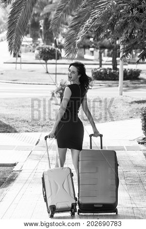 Happy woman walks and rolls two suitcases wheeled travel bags on street pavement on sunny summer day on cityscape background black and white