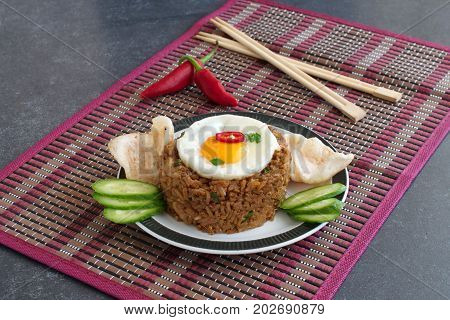 Nasi goreng fried rice with shrimps and egg garnished with fresh cucumber slices and prawn crackers on a plate on a cloth. Asian food