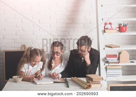 Home schooling and back to school concept. Teachers and schoolgirl on classroom background. Kid and tutors with serious faces. Girl lady with glasses and bearded man sit at desk and write in notebook