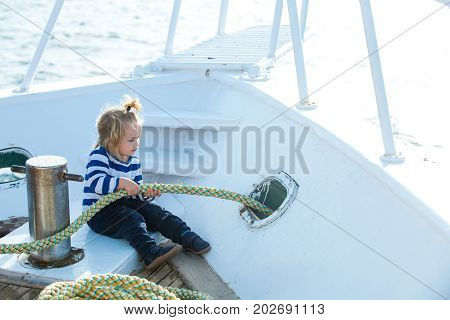 Travel and summer vacations. Little child sitting and berthing rope on white boat. Boy kid playing with rope on yacht. Baby care and childhood. Yachting and sailing concept.