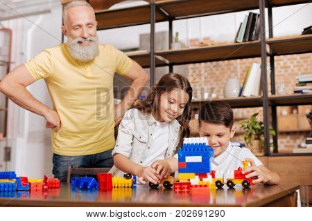 Delight for eyes. Happy elderly man standing with his hands on waist and looking fondly at his beloved grandchildren play with car models made out of a construction set pieces