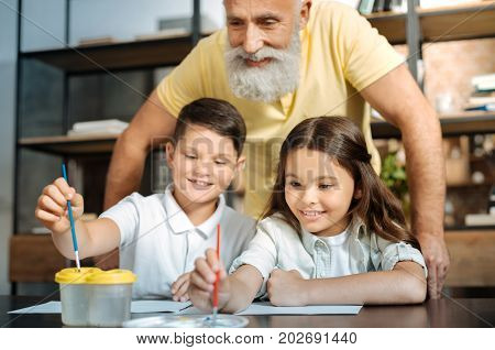 Proud grandfather. Happy elderly man standing behind his beloved grandchildren and watching them wash the brush in a water container and choose a color from the palette