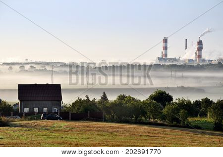Pipes of working Nitrogen plant in smoke in summer morning. Abandoned village in the foreground. Grodno, Belarus.