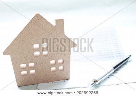 Business, finance, saving money, banking, property loan or mortgage concept :  Wood house model, saving account book or financial statement and coins scattered from glass jar on office desk table