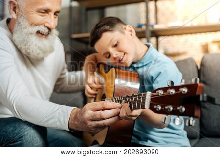 Teaching with pleasure. Merry elderly man teaching his beloved grandson how to play guitar and strum chords while smiling happily