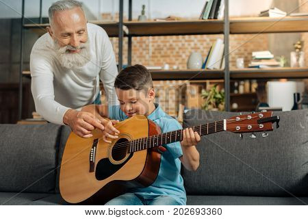 Helpful tips. Pleasant loving grandfather giving his pre-teen grandson a piece of advice on how to strum chords correctly while the boy learning how to play guitar