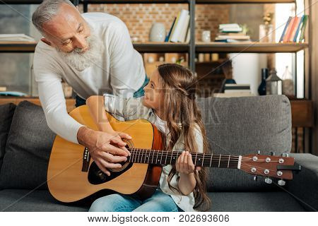 Path to dream. Adorable little girl learning how to play a guitar while her beloved grandfather showing her to strum chords on guitar