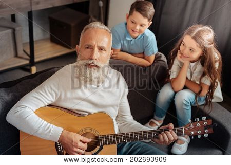 Grateful audience. Inspired elderly man playing guitar and singing for his grandchildren while they listening to him with admiration
