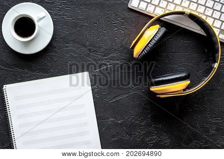Desk of musician with blank paper and headphones for songwriter work set on dark background top view mockup