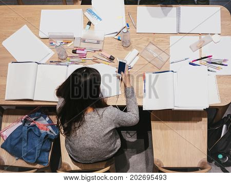 Student Top view holding phone with Book documents on table College lifestyle