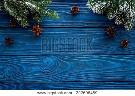 New year frame. Spruce branch and pine cones on wooden background top view copyspace.
