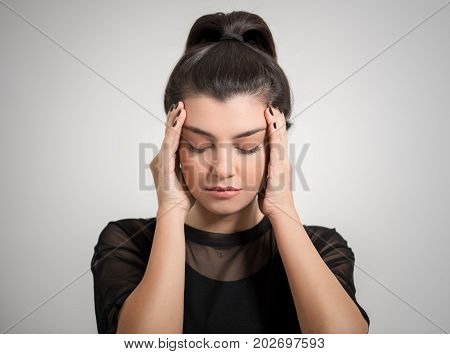 Portrait of beautiful young brunette with bare shoulders touching her temples feeling stress, on gray background