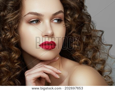Brunette Girl With Long And Shiny Wavy Hair . Beautiful Model With Curly Hairstyle. Red Lips