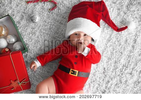 Cute little baby in Santa costume on soft fabric