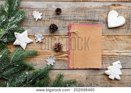 Christmas eve set with spruce branches, notebook and pine cones on wooden background top veiw mock-up