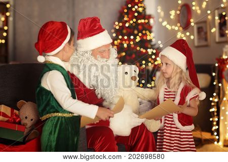 Cute elf kids showing letters to Santa in room with beautiful Christmas decoration
