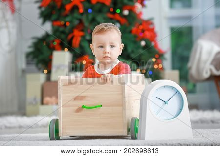 Cute little baby with toy cart and clock at home. Christmas countdown concept