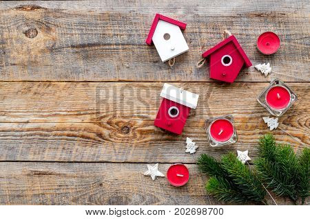 house toys and candles to decorate christmas tree for new year celebration with fur tree branches on wooden table background top veiw mockup