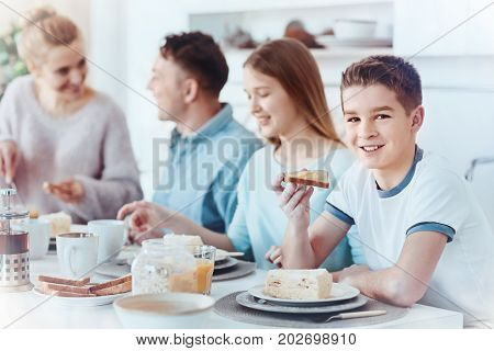 Family time. Selective focus on a cheerful boy holding a yummy toast with honey and smiling for the camera while sitting next to his family during a breakfast.