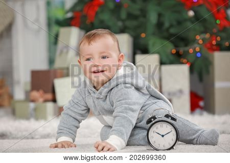 Cute little baby with clock at home. Christmas countdown concept