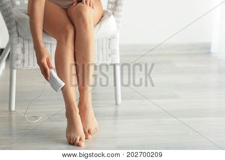 Beautiful young woman epilating legs at home