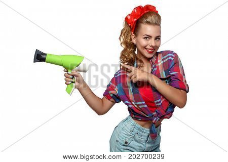 Half body portrait of young woman in pinup clothes with hairdryer pointing by finger