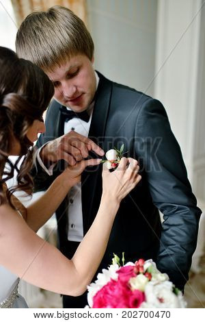 Groom and bride are wearing a boutonniere indoors. Male portrait of handsome guy. Beautiful model boy in colorful wedding clothes. Man is posing