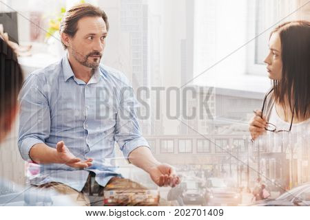 Professional help. Distressed adult man talking about his problems while a female psychologist conducting a group session
