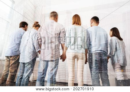 One spirit. Rear view of group of people holding their hands and standing together while having a psychological session