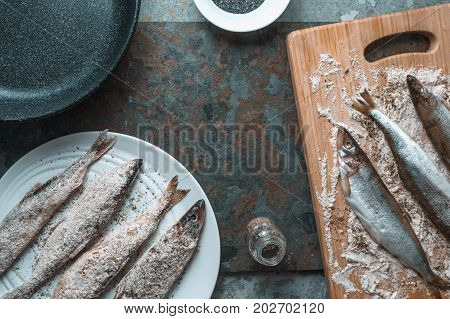 Smelt on a plate and on a cutting board, frying pan horizontal