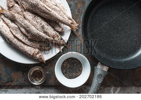 Smelt on a plate, frying pan, salt and spices horizontal
