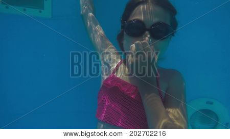 The little girl in water park swimming underwater and smiling