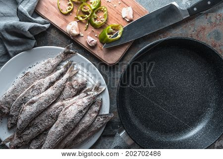 Chili and garlic, smelt on a plate and frying pan horizontal