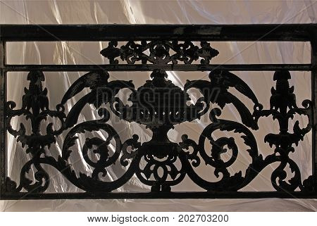 Window with decorative railing from black smithery iron on a neutral background. 13-15 rue Croissant Paris France. August 31 2017