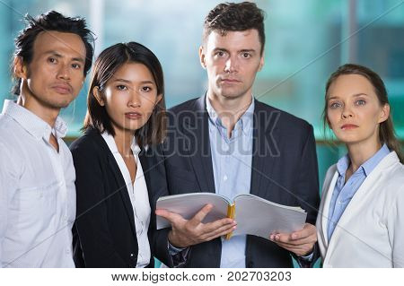Closeup of middle-aged serious business man holding open book and three people standing around him with blurred view in background. They are looking at camera.