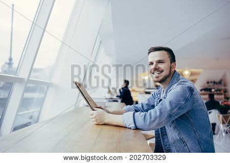 Handsome guy is sitting in front of the table near window. Smiling young student has coffeebreak. He is looking at camera and making order