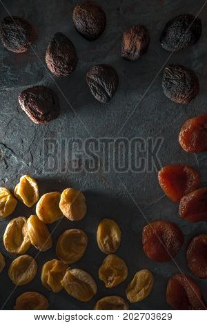 Yellow, orange and brown dried apricots on a blue stone vertical