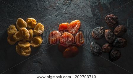 Multicolored dried apricots on a gray stone horizontal