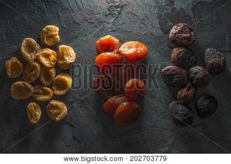 Groups of colorful dried apricots on a gray stone horizontal