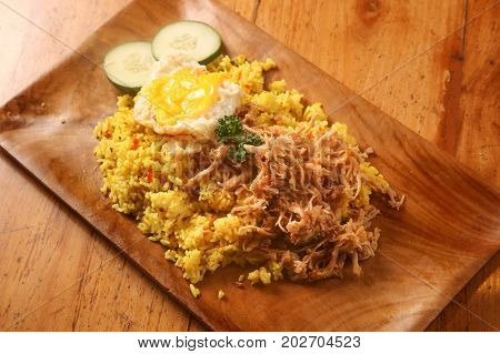 Fried rice served with egg and cucumber slices