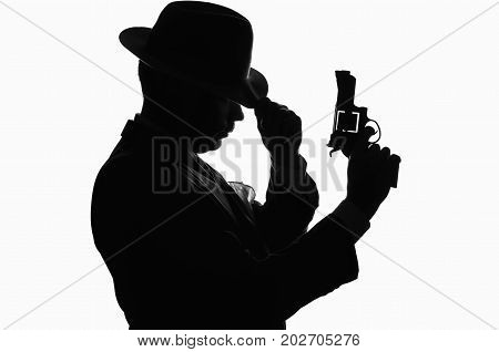 Silhouette of a private detective with a gun in right hand. Gangster looks like mafiosi Al Capone and stay side to camera. He wears a mob jacket. Police criminal scene in black and white. Studio shot isolated or cutout from background.