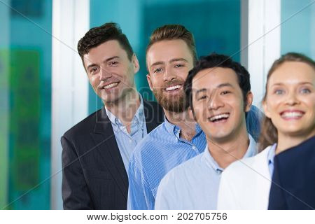 Cheerful handsome men standing in line with colleagues and looking at camera. Positive young specialist working in large company. Staff concept
