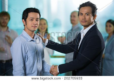 Confident Asian business partners shaking hands and looking at camera. Serious boss touching employees shoulder as symbol of support while congratulating with new job. Business relationship concept