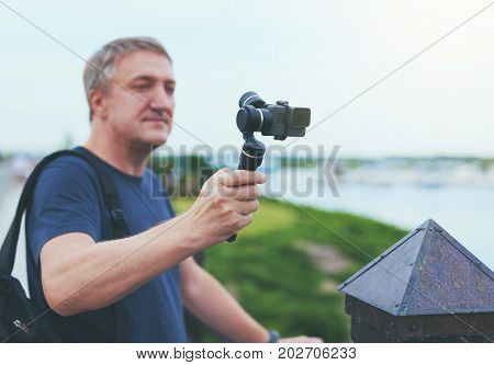 Man capturing filming with small personal camera a park, shallow depth of focus, focus on camera