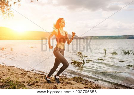 A Beautiful Sporty Woman Runing On The Shore Of A Lake In Sportswear. Girl Is Exercising