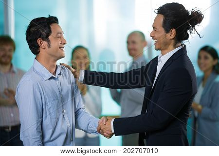 Optimistic business colleagues talking while shaking hands and looking at each other. Happy boss congratulating new employee. People clapping in background. Business event concept